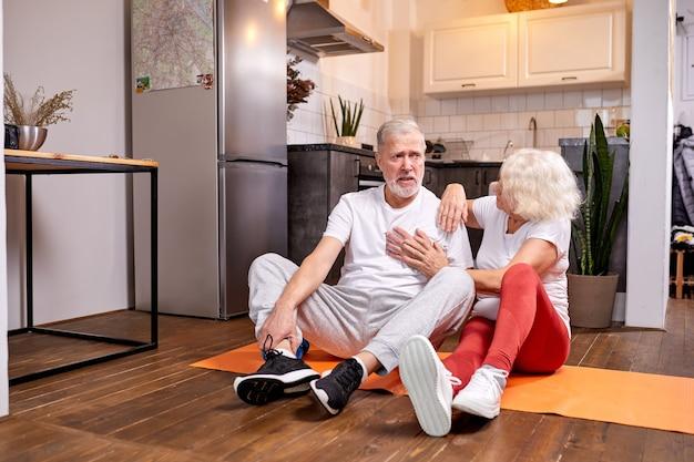 Ältere männer fühlen sich nach körperlicher aktivität schlecht, frauen unterstützen und helfen ihm, sie sitzen nach dem yoga auf dem boden