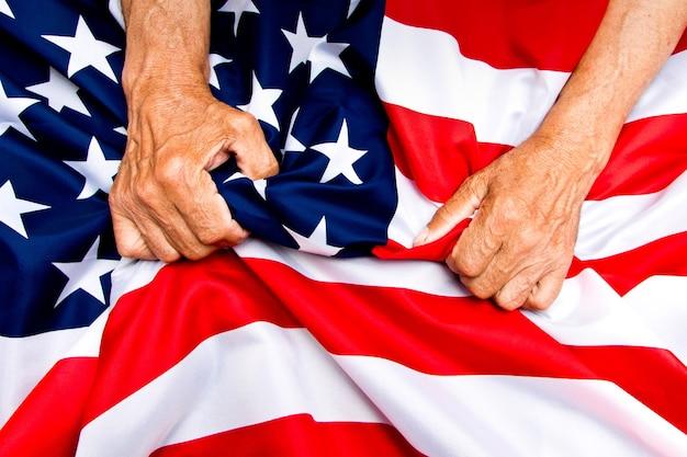Ältere männer hände komprimieren eine usa-flagge als konzept der pflege von rentnern