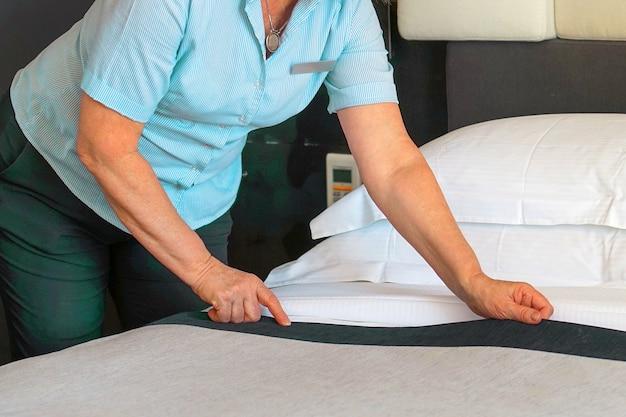 Ältere magd, die bett im hotelzimmer macht. haushälterin macht bett