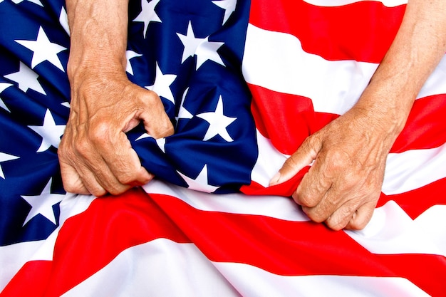 Ältere mannhände, die eine usa-flagge halten