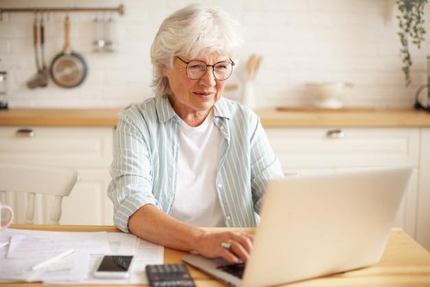 Ältere menschen, elektronische geräte und lifestyle-konzept. porträt der aufgeregten frau beim ruhestand, der online mit laptop einkauft. ältere frau, die glücklich aussieht, weil sie endlich alle ihre schulden bezahlt hat