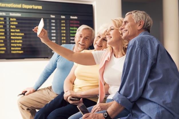 Ältere menschen sitzen im wartezimmer am flughafen.