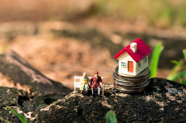 Ältere miniaturleute, die mit minihaus auf stapel sitzen, prägen unter verwendung als jobruhestand und familienkonzept