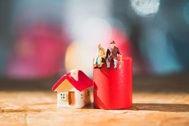 Ältere miniaturmenschen, die auf rotem holzblock mit minihaus sitzen, das als arbeitsrente und familienkonzept verwendet
