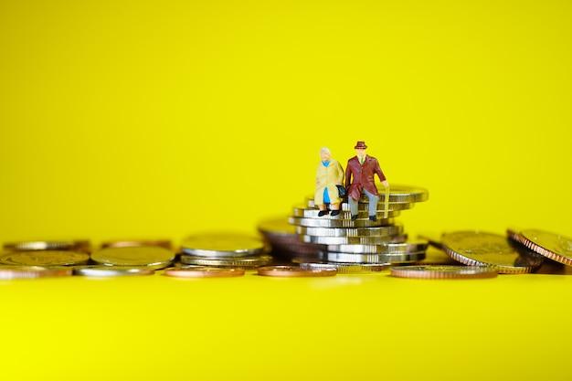 Ältere miniaturmenschen, die auf stapelmünzen sitzen, die als arbeitsruhestands-, geschäfts- und versicherungskonzept verwenden