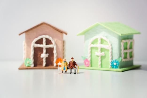 Ältere miniaturmenschen, die mit minihaus sitzen