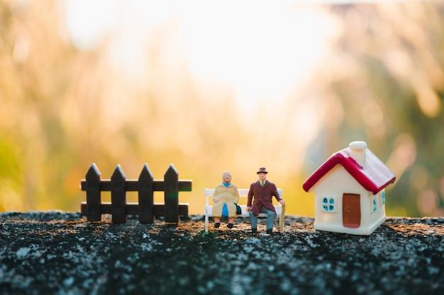 Ältere miniaturmenschen, die mit minihaus verwenden als job-ruhestand und familienkonzept sitzen