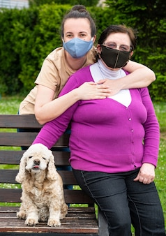 Ältere mutter mit tochter in medizinischen gesichtsmasken, die im park entspannen
