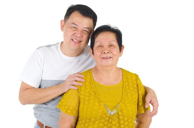 Ältere mutter und erwachsene nachkommen der glücklichen asiatischen familie, die spaßzeit am innenstudio haben.