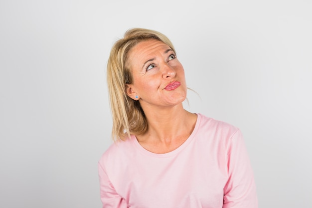 Ältere nachdenkliche frau in rosafarbener bluse