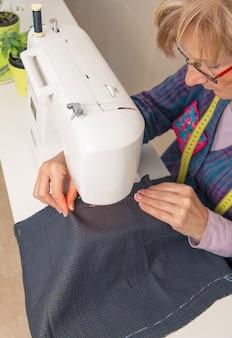 Ältere näherinfrau, die mit kleidungsstück an einer nähmaschine arbeitet. selektiver fokus auf frauengesicht.