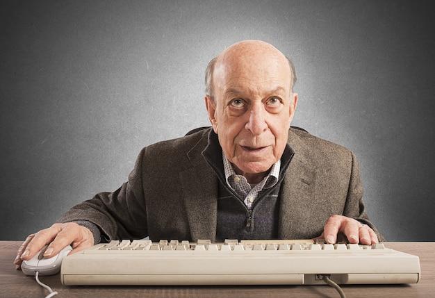 Ältere nerds arbeiten mit seiner vintage-tastatur