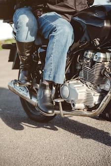 Ältere paarbeine mit stiefeln, die über dem motorrad sitzen, bereit zu gehen