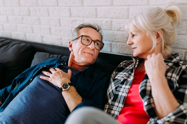 Ältere paare auf couch im ruhestandshaus