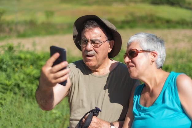 Ältere paare auf der wanderung, die ein selfie nimmt