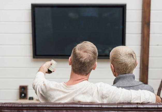 Ältere paare der hinteren ansicht, die etwas im fernsehen aufpassen