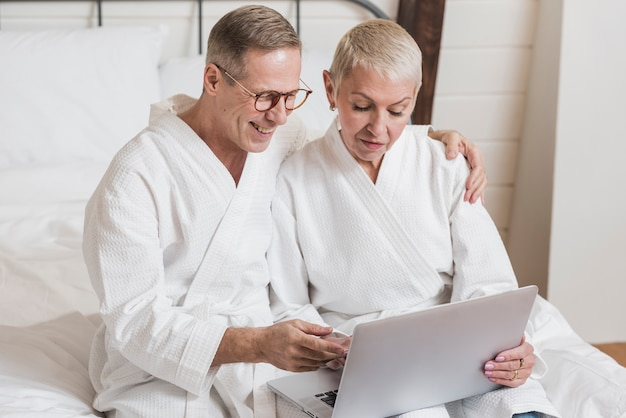 Ältere paare der vorderansicht, die auf einem laptop im bett schauen