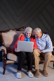 Ältere paare der vorderansicht unter verwendung eines laptops