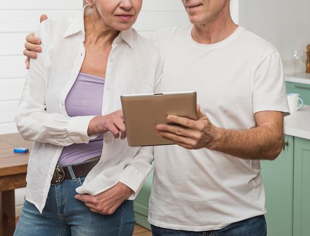 Ältere paare des mittleren schusses, die auf einer tablette schauen
