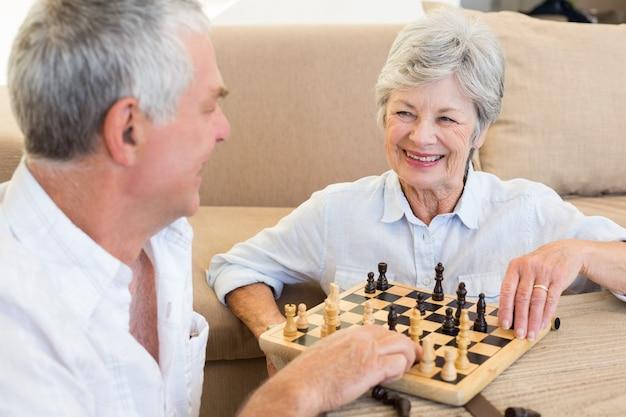 Ältere paare, die auf dem fußboden spielt schach sitzen