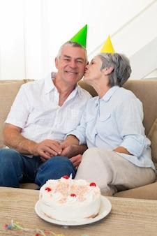 Ältere paare, die auf der couch feiert einen geburtstag sitzen