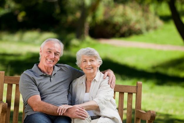 Ältere paare, die auf einer bank sitzen