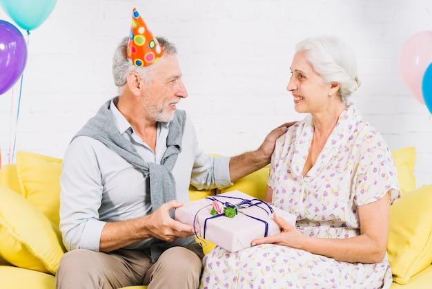 Ältere paare, die auf sofa mit geburtstagsgeschenk sitzen