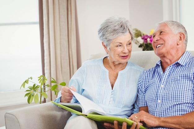 Ältere paare, die auf sofa sitzen und ein buch im wohnzimmer lesen