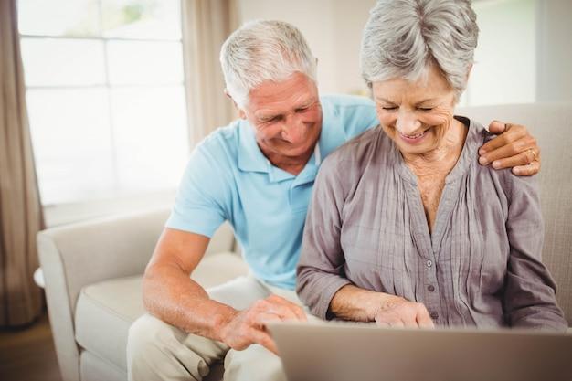 Ältere paare, die auf sofa sitzen und laptop im wohnzimmer betrachten