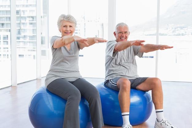 Ältere paare, die das ausdehnen tun, trainiert auf eignungsbällen