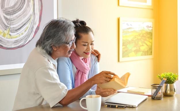 Ältere paare, die den gebrauch des laptops studieren.