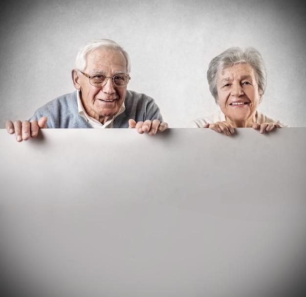 Ältere paare, die ein leeres brett halten