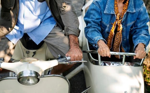 Ältere paare, die einen klassischen roller reiten