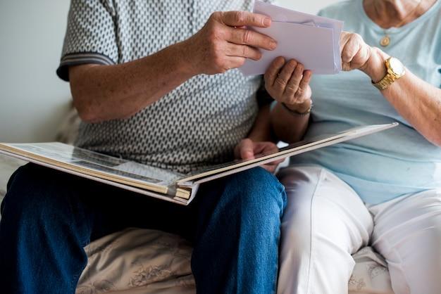 Ältere paare, die familienfotoalbum betrachten