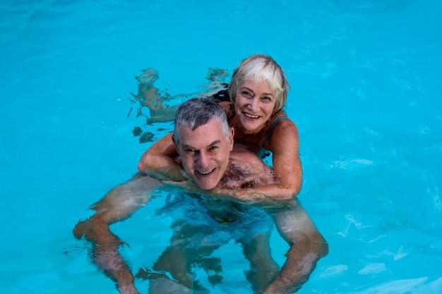 Ältere paare, die im swimmingpool genießen