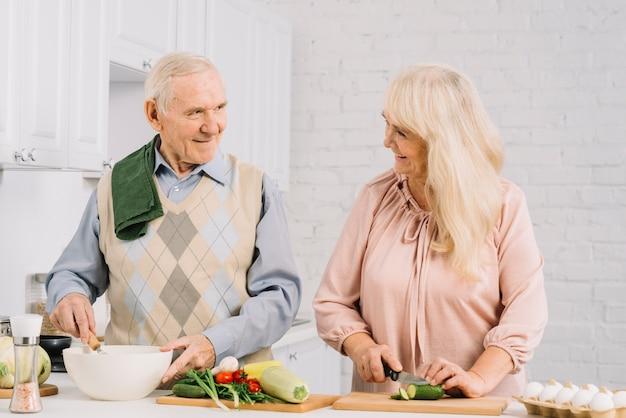 Ältere paare, die in der küche kochen