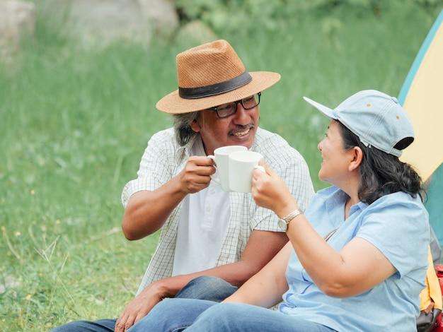 Ältere paare, die kampierenden ausflug genießen, trinken sie kaffee morgens zusammen.