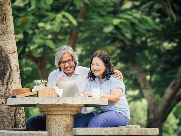 Ältere paare, die laptop schauen und frühstücken zusammen im garten.