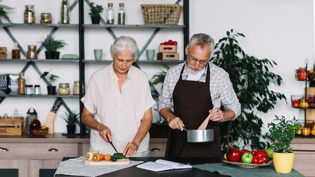 Ältere paare, die lebensmittel in der küche zubereiten