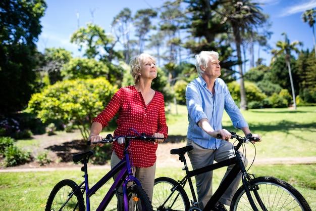 Ältere paare, die mit fahrrad im park gehen