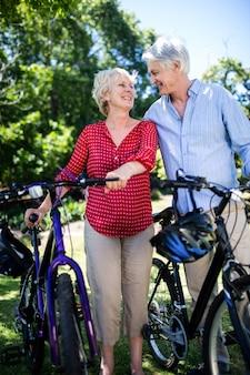 Ältere paare, die mit fahrrad im park stehen