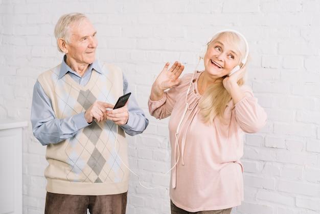 Ältere paare, die musik auf smartphone hören