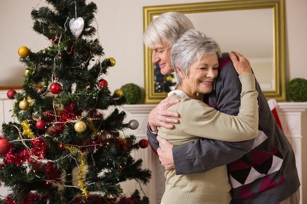 Ältere paare, die neben ihrem weihnachtsbaum umarmen
