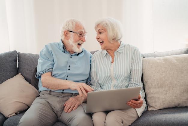 Ältere paare, die online im internet mit computer-laptop zu hause einkaufen - schöne glückliche senioren, die pc- und social-network-apps verwenden using
