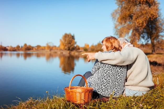 Ältere paare, die picknick durch herbstsee haben glückliches mann- und frauenumarmen