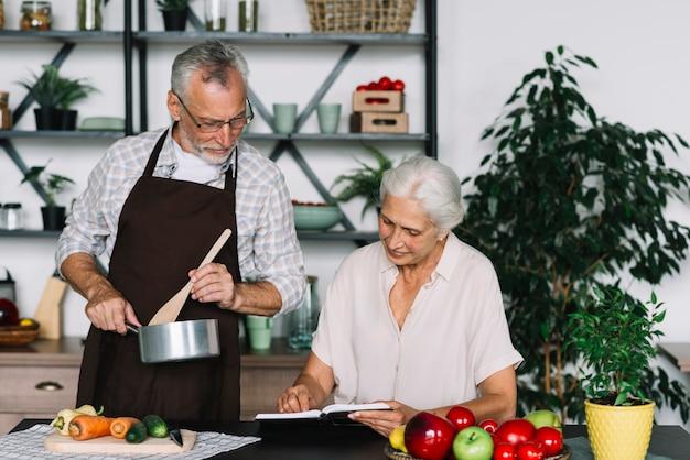 Ältere paare, die rezept in der küche betrachten