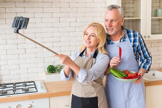 Ältere paare, die selfie am handy in der küche nehmen