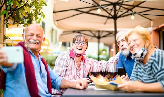 Ältere paare, die selfie an der restaurantbar mit gesichtsmasken nehmen