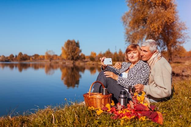 Ältere paare, die selfie beim haben des picknicks durch herbstsee nehmen