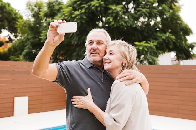 Ältere paare, die selfie im garten nehmen